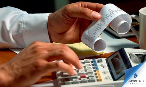Кассовый чек в руках и счетная машина