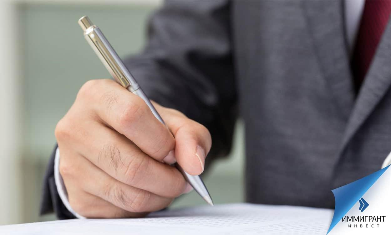 Рука с ручкой над листами бумаги
